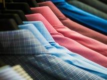Camisas comprobadas del ` s de los hombres que cuelgan en el estante fotografía de archivo