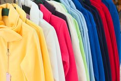 Camisas de deporte multicoloras que cuelgan en almacén imágenes de archivo libres de regalías