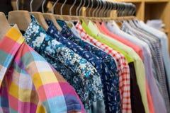 Camisas de los hombres coloreados que cuelgan en tienda Imagen de archivo
