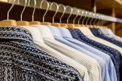 Camisas de los hombres que cuelgan en tienda Fotografía de archivo