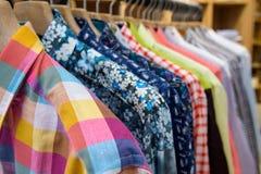 Camisas de los hombres que cuelgan en tienda Imagenes de archivo