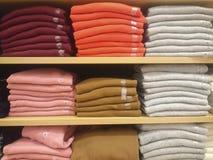 Camisas del ` s de los hombres en estantes de una tienda fotografía de archivo