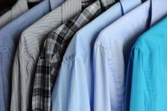 Camisas do ` s dos homens em ganchos, azul, cinzento e quadriculado Foto de Stock