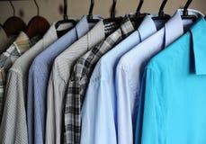 Camisas do ` s dos homens em ganchos, azul, cinzento e quadriculado Fotografia de Stock