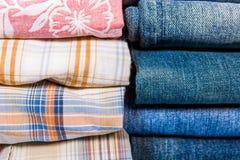 Camisas e calças de brim de manta empilhadas Foto de Stock Royalty Free