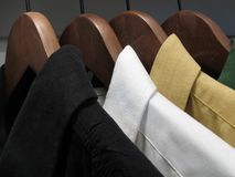 Camisas en perchas de madera imagenes de archivo