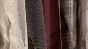 Camisas masculinas clássicas que penduram no trilho da roupa filme