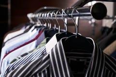 Camisas para hombre en diversos colores en suspensiones Imágenes de archivo libres de regalías