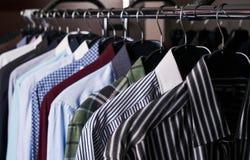 Camisas para hombre en diversos colores en suspensiones fotografía de archivo