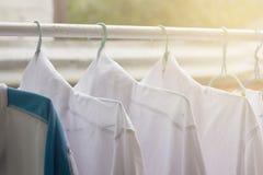 Camisas que cuelgan encendido en el carril o la ropa abierto al aire libre el día del lavadero foto de archivo libre de regalías