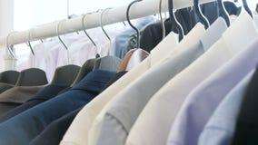 Camisas, ternos de negócio e t-shirt em uma loja em um gancho filme