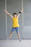 Camiseta amarilla que lleva adolescente joven y salto fotos de archivo