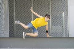 Camiseta amarilla que lleva adolescente joven y salto fotografía de archivo