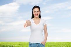 Camiseta blanca del womanin feliz que muestra los pulgares para arriba Foto de archivo libre de regalías