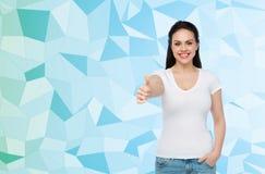 Camiseta blanca del womanin feliz que muestra los pulgares para arriba Imagenes de archivo