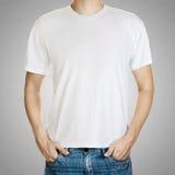 Camiseta blanca en un modelo del hombre en fondo gris Foto de archivo libre de regalías