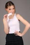 Camiseta blanca que lleva de la muchacha y tarjeta bitting Cierre para arriba Fondo gris Fotografía de archivo