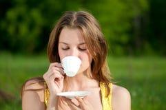 Camiseta caliente de la bebida hermosa de la mujer joven al aire libre Foto de archivo