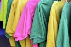 Camiseta colorida en perchas Foto de archivo libre de regalías