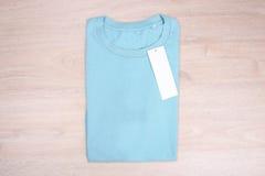 Camiseta del azul de cielo en fondo de madera Fotografía de archivo libre de regalías