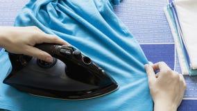 Camiseta del azul que plancha de la mano del ` s de la mujer en el tablero que plancha imagen de archivo libre de regalías