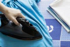 Camiseta del azul que plancha de la mano del ` s de la mujer en el tablero que plancha foto de archivo