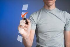 Camiseta del hombre joven que comprueba la caja de la lista de control Fondo para una tarjeta de la invitación o una enhorabuena Fotografía de archivo libre de regalías