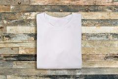 Camiseta doblada blanca del espacio en blanco en fondo de madera foto de archivo libre de regalías