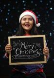 Camiseta e Santa Hat Holding Merry vestindo do Natal da menina asiática foto de stock