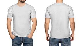 Camiseta gris en un fondo blanco, un frente y una parte posterior del hombre joven imagen de archivo