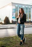 Camiseta que lleva de la muchacha de la moda, vaqueros y chaqueta de cuero presentando contra la calle, estilo urbano de la ropa imagen de archivo libre de regalías