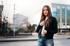 Camiseta que lleva de la muchacha y chaqueta de cuero que presentan contra la calle, estilo urbano de la ropa imagen de archivo libre de regalías