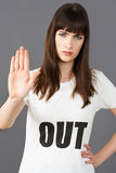 Camiseta que lleva del partidario de la mujer joven impresa con HACIA FUERA lema fotos de archivo