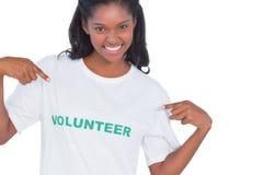 Camiseta voluntaria que lleva sonriente de la mujer joven y el señalar a él Imagen de archivo libre de regalías