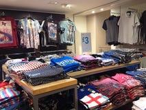 Camisetas brillantemente coloreadas dobladas en una tienda Imagen de archivo libre de regalías