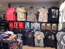 Camisetas brillantemente coloreadas en los estantes en una tienda Fotos de archivo