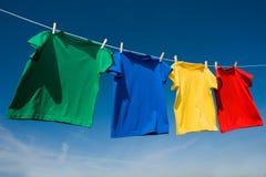 Camisetas coloreadas primarias en una cuerda para tender la ropa Imagen de archivo libre de regalías