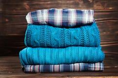 Camisetas feitas malha de lãs A pilha do inverno feito malha, outono veste-se no fundo de madeira, camisetas, malhas Imagens de Stock