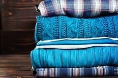 Camisetas feitas malha de lãs A pilha do inverno feito malha, outono veste-se no fundo de madeira, camisetas, malhas Imagem de Stock
