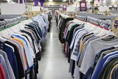 Camisetas hechas punto que cuelgan en dos filas en suspensiones en la tienda borrosa La v?spera de Black Friday foto de archivo