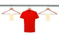 Camisetas rojas en las suspensiones y las etiquetas en blanco aisladas en el backgro blanco Fotografía de archivo libre de regalías