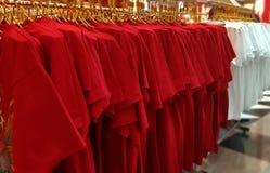 Camisetas rojas y blancas que cuelgan en el estante Imágenes de archivo libres de regalías