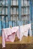 Camisola e t-shirt que penduram em uma linha de roupa Fotos de Stock Royalty Free