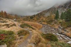 Camminando all'autunno in un giorno nuvoloso in una valle della montagna Fotografia Stock
