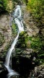 Camminando attraverso una foresta meravigliosa della montagna, ho scoperto una cascata splendida che cade da una considerevole al immagine stock