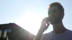 Camminando e parlando sul telefono durante il tramonto, davanti al Sun Fotografie Stock Libere da Diritti