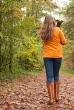 Camminando indietro nella foresta con un cane Immagine Stock