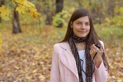 Camminando nella sosta d'autunno con il mp3 ed i trasduttori auricolari Fotografie Stock