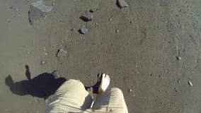 Camminando su una spiaggia di sabbia nera stock footage