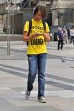 Camminando sull'adolescente di area che usando il suo iPhone Immagini Stock